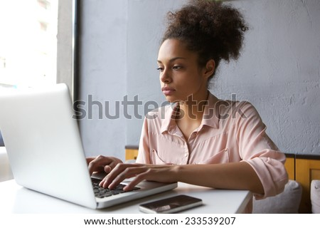 Close up portrait of a young woman working on laptop - stock photo