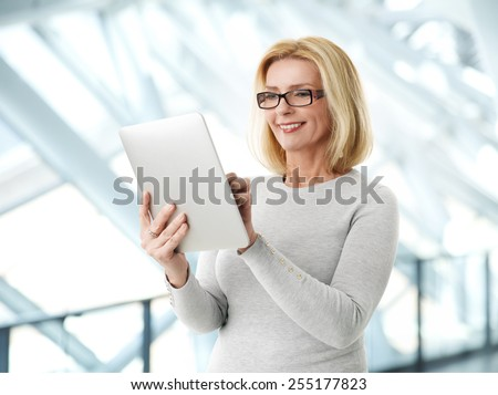 Close-up portrait of active business woman holding laptop while standing at office.  - stock photo