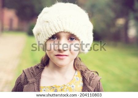 Close-up portrait of adorable child girl wearing white cap  - stock photo