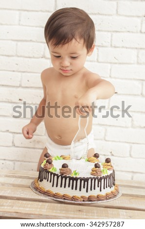 close up portrait of adorable handsome toddler trying to cut his cake - stock photo