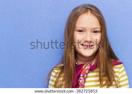 Close up portrait of adorable little girl of 8-9 years old against purple background - stock photo