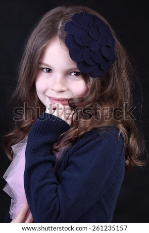 Close-up portrait of adorable smiling child girl in hat. Portrait of a beautiful girl with an English hat on his head. - stock photo