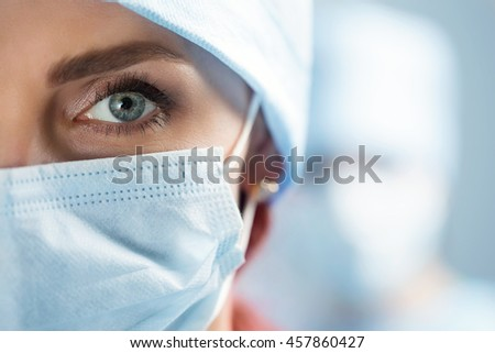 Close up portrait of adult female surgeon doctor wearing protective mask and cap. Half face closeup. Healthcare, medical education, emergency medical service and surgery concept - stock photo