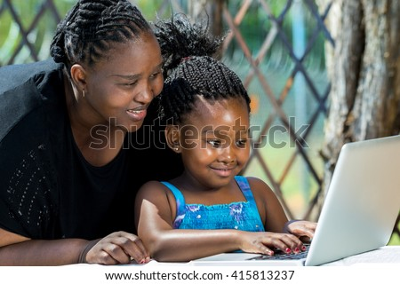 Close up portrait of African mother and little girl with braided hairstyle looking at laptop. Cute girl typing on keyboard at table in garden. - stock photo
