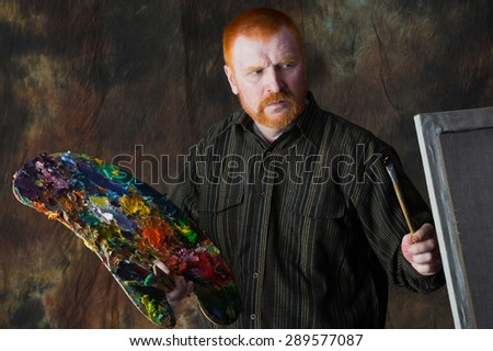close-up portrait of an adult male artist with red hair and a beard at work studio on dark background - stock photo