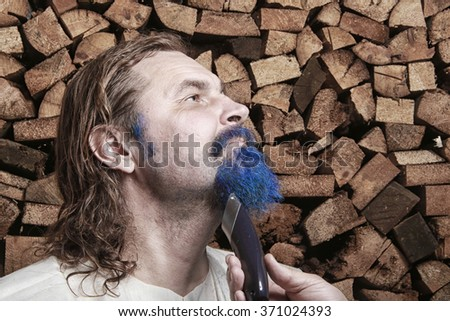 close-up portrait of an adult man with a blue beard and mustache, long blond hair in tissue Cape, shaving of beards on background stack of firewood in the bath - stock photo