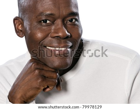 Close-up portrait of an afro American mature man smiling with hand on chin in studio on white isolated background - stock photo