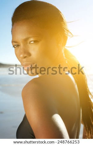 Close up portrait of an attractive african american woman at the beach - stock photo