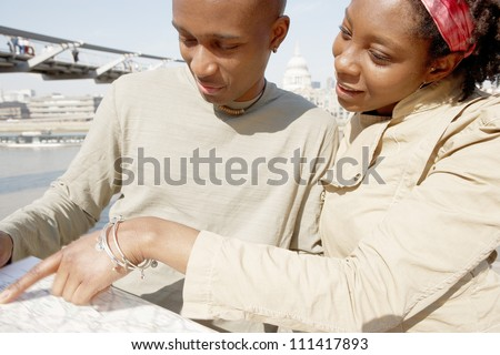 Close up portrait of an attractive black couple pointing at a guide map on vacation while standing by the Millennium Bridge and St Paul's Cathedral in London's river Thames. - stock photo