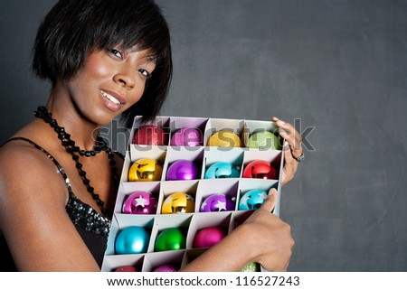 Close up portrait of an attractive black woman holding a box full of various christmas bar balls against a dark background. - stock photo