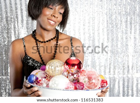 Close up portrait of an attractive black woman holding a dish full of christmas bar balls against a silver sequins background. - stock photo