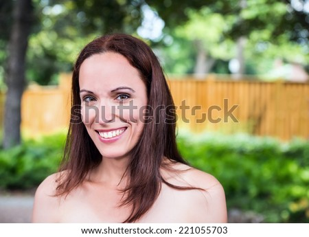 Close up portrait of an attractive brunette woman in her late 30's or early 40s outside in a park like setting on a sunny day during the summer season.  Room for copy space.  - stock photo