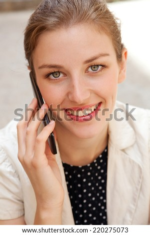 Close up portrait of an attractive business woman using a smartphone having phone call conversation in a city street, smiling outdoors. Professional people and technology. - stock photo