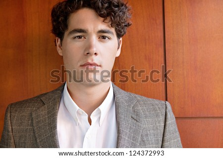 Close up portrait of an attractive businessman wearing an elegant suit and standing against a luxurious wooden wall, looking at the camera. - stock photo