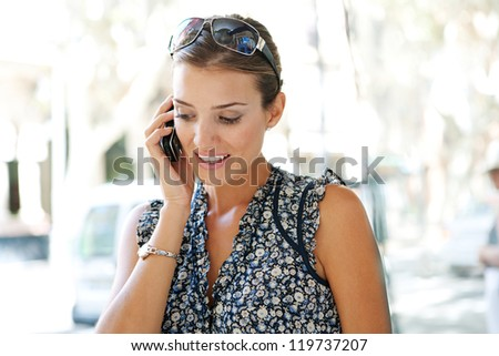 Close up portrait of an attractive businesswoman having a conversation on her smart phone in a classic city, outdoors. - stock photo