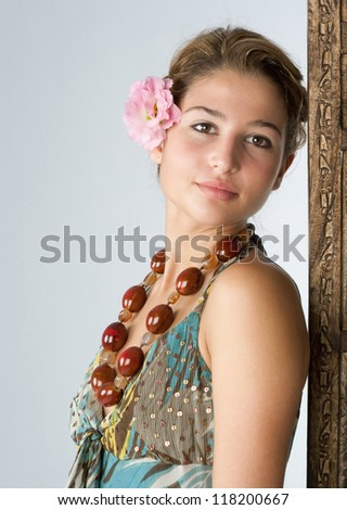 Close up portrait of an attractive exotic young woman wearing tropical clothes and standing next to a wooden screen panel at a health spa, smiling. - stock photo