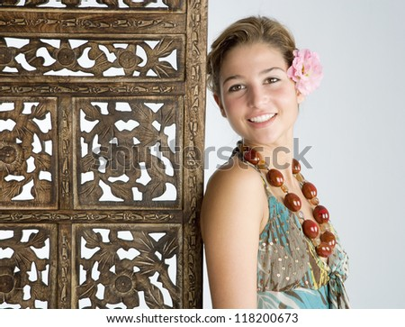 Close up portrait of an attractive exotic young woman wearing tropical clothes and standing next to a carved wood screen panel. - stock photo