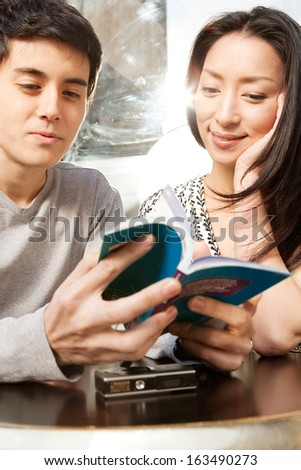 Close up portrait of an attractive Japanese tourist couple sitting at a cafe shop terrace in a destination city during a sunny day, reading a guide book with reflections of direct sun light, outdoors. - stock photo