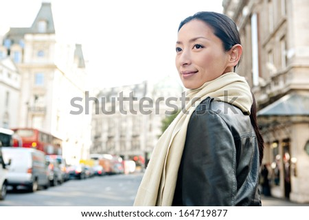 Close up portrait of an attractive Japanese tourist woman visiting the city of London turning while standing on a classic architecture grand street with space and sunny skies, outdoors. - stock photo