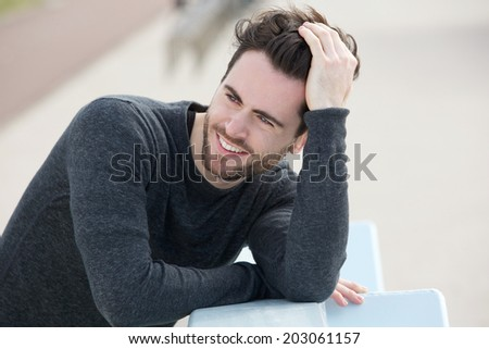 Close up portrait of an attractive man smiling with hand in hair - stock photo