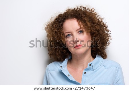 Close up portrait of an attractive older woman with curly hair posing against white background - stock photo