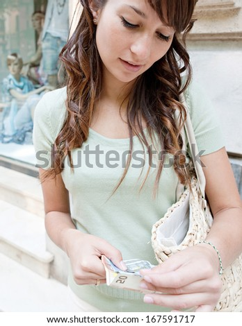 Close up portrait of an attractive teenager woman counting bank notes currency money while standing by a store display window during a shopping day out, outdoors. - stock photo