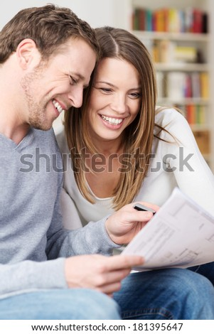 Close up portrait of an attractive young couple laughing as they discuss paperwork together at home in the living room - stock photo