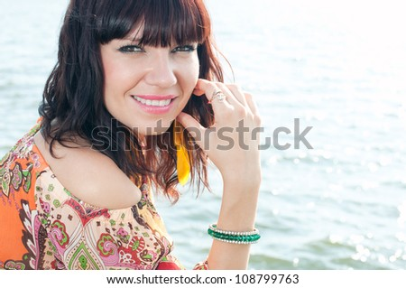 Close-up portrait of an attractive young female standing near the shore - stock photo