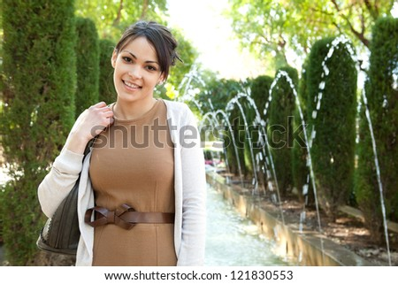 Close up portrait of an attractive young tourist woman standing near a fountain in a botanic garden, holding her handbag, outdoors. - stock photo