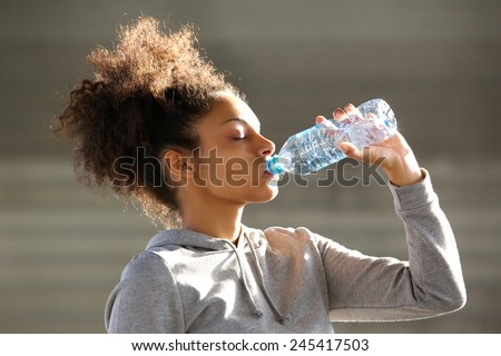 Close up portrait of an attractive young woman drinking water from bottle - stock photo