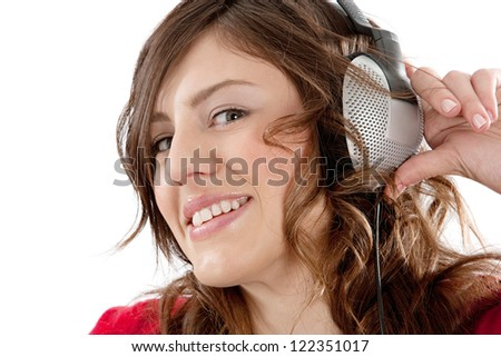 Close up portrait of an attractive young woman listening to music while holding her headphones, isolated against a white background. - stock photo