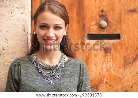 Close up portrait of an attractive young woman relaxing against an old textured stone wall and wooden entrance door, smiling at the camera during sunny day on vacation. Outdoors lifestyle. - stock photo