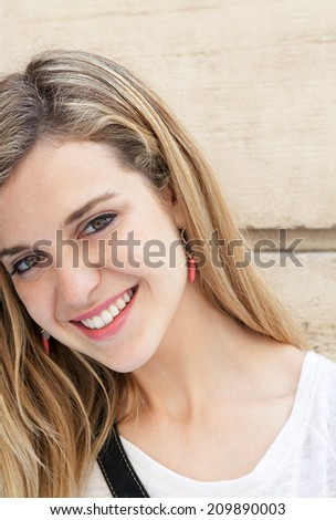 Close up portrait of an attractive young woman relaxing outdoors, smiling and looking at the camera with joyful friendly expressions. Young people lifestyle. - stock photo