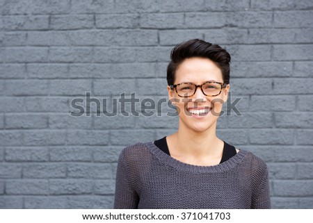 Close up portrait of an attractive young woman smiling with glasses - stock photo