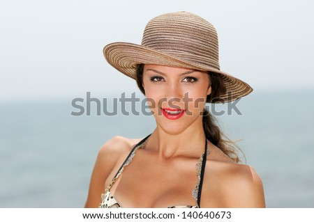Close up portrait of an beautiful woman smiling with a sun hat on a tropical beach - stock photo