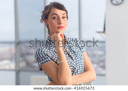 Close-up portrait of an elegant ambitious young woman, holding arms crossed, wearing checkered shirt. - stock photo