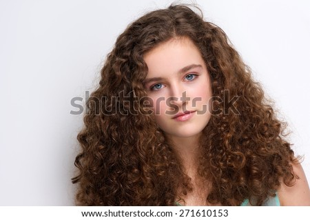 Close up portrait of an elegant teenage girl with long curly hair - stock photo