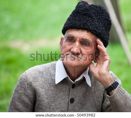 Close up portrait of an old farmer over blurred green background - stock photo