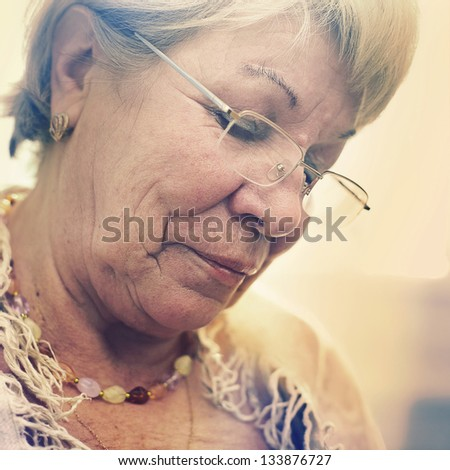 Close up portrait of an old grandmother in glasses - stock photo