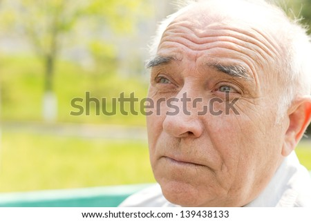 Close up portrait of an old man over the blurred background - stock photo