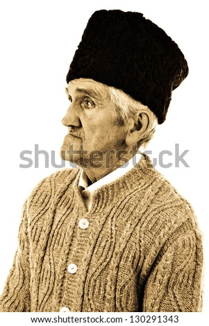 Close-up portrait of an old peasant man with wooly hat isolated on white background - stock photo