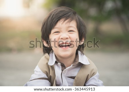 Close up portrait of asian boy laughing,vintage filter - stock photo