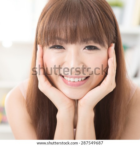 Close up portrait of Asian girl hands holding face, relaxed and smiling at home, woman living lifestyle indoors. - stock photo