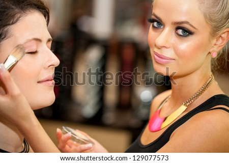 Close up portrait of attractive female make up artist at work. - stock photo