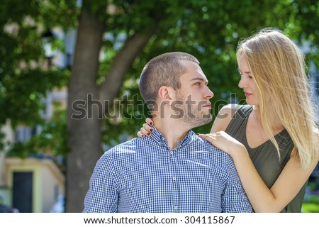 Close up portrait of attractive girl embracing her boyfriend outdoors. Summer Street City - stock photo