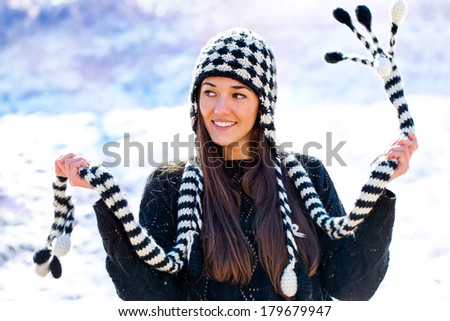 Close up portrait of attractive girl playing with scarf in snow. - stock photo