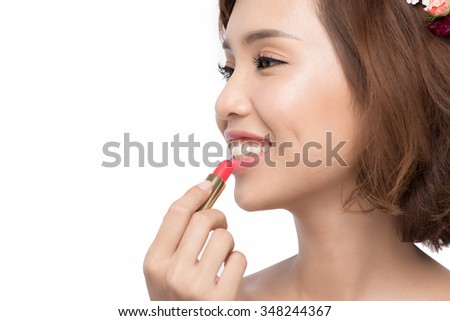 Close up portrait of attractive girl rouging her lips. She is holding red lipstick. Her mouth is gently open. Isolated on grey background - stock photo