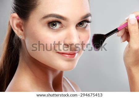 close up portrait of attractive model smiling while tidy up her make up using fan brush - stock photo