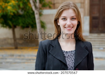 Close up portrait of attractive young businesswoman confidently smiling at the camera while standing in the city, outdoors. Business and professional working people. - stock photo