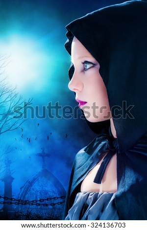 Close up portrait of attractive young mysterious Gothic girl wearing black hood.Graveyard with full moon in background. - stock photo